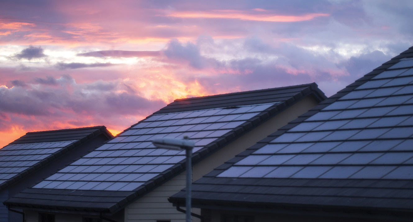 Solar panels on rooftop at sunset.
