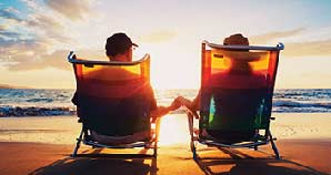 Retired couple sitting on beach watching the sunset.